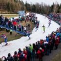 Našlapaný areál Břízky žene závodníky ke střelnici, biatlonová exhibice 2015